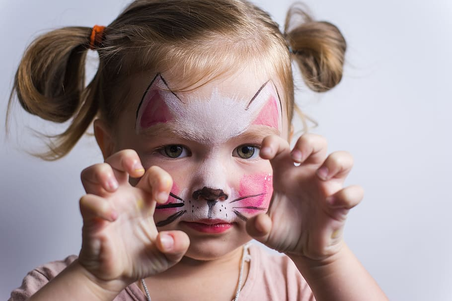 Child wearing Halloween makeup for a cat costume